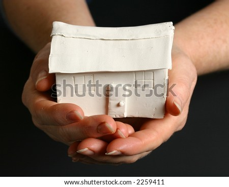 Two hands holding a small house - stock photo