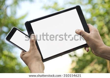 Two hands holding an electronic tablet and a smart phone, both with white screens, for presentation and mock-ups for apps. - stock photo