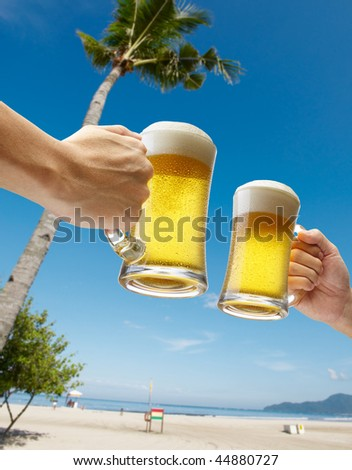 two hands holding beers toasting on beach - stock photo