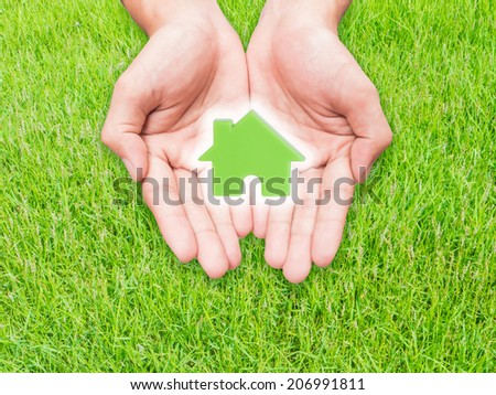 Two hands holding green house  model over green grass field