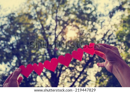 two hands holding hearts with boca background and sun with retro instagram filter - stock photo