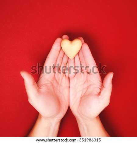 Two hands, holding little wooden heart genly on red background. Saving love concept. Greeting to Saint Valentines day. - stock photo