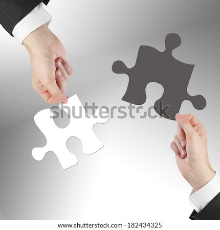 two hands holding puzzle isolated on gray - stock photo