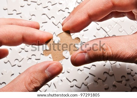 two hands holding puzzle piece - stock photo