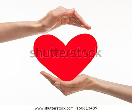 Two hands holding red heart on white background