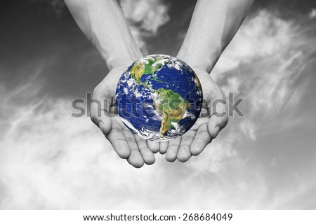 Two hands holding the color earth in black and white concept . Elements of this image furnished by NASA - stock photo