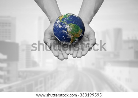 Two hands holding the color earth in black and white concept:human hands healing and save the earth planet ecology conceptual:safe environment concept:Elements of this image furnished by NASA - stock photo