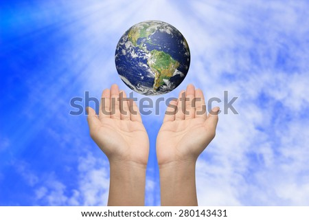 Two hands holding the earth on blurred blue sky backgrounds. Elements of this image furnished by NASA - stock photo