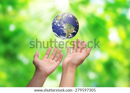 Two hands holding the earth on blurred green nature backgrounds. Elements of this image furnished by NASA - stock photo