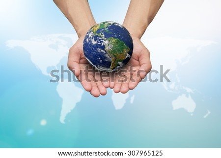 Two hands holding the earth on world map with colorful blue sky background:man protect/save the planet life:earth day concept:Elements of this image furnished by NASA.safe and healing world concept. - stock photo