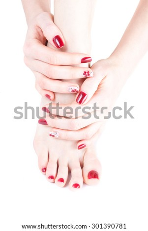 two hands holding the foot gently and carefully, on fingers manicure and pedicure with red nail polish and painted flowers, isolated on white background