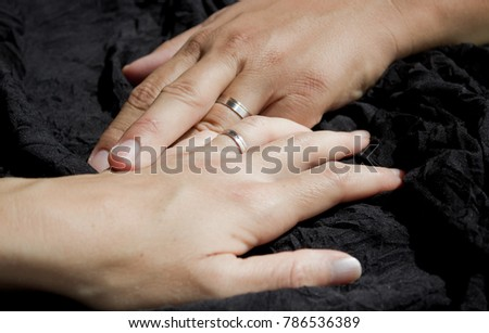 two hands holding wedding rings, touching each other, on black background