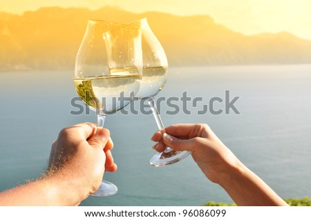 Two hands holding wineglases against vineyards in Lavaux region, Switzerland - stock photo