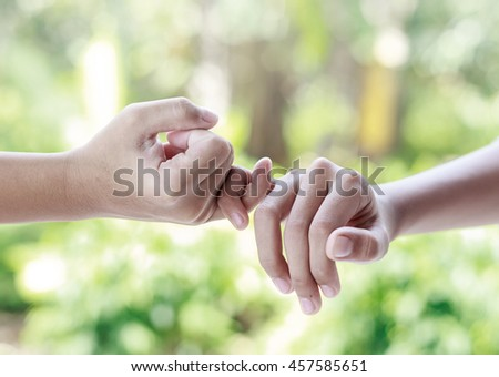Two hands hook each other's little finger concept of promise