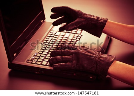 Two hands in black leather gloves stealing information from a mobile computer. On-line or Internet identity theft concept. - stock photo