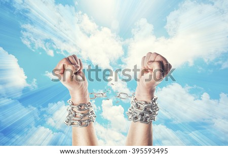 Two hands in chains on a heavens background with a flash - stock photo