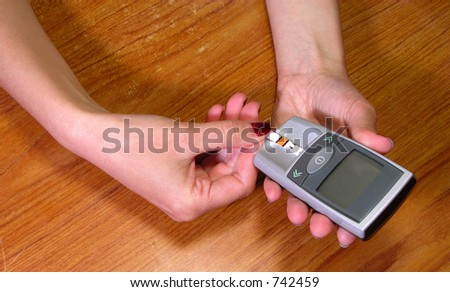 Two hands introducing a glicemic test strip in the glucometer on a wooden desk-educational image for diabetes patients.