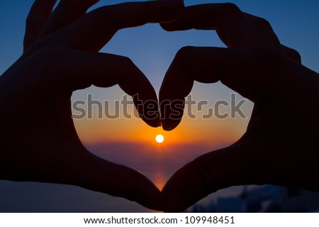 Two hands make a heart by sunset - stock photo