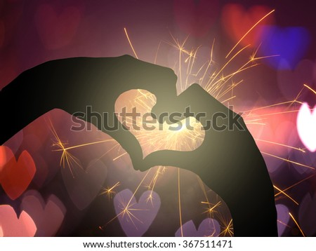 two hands making a heart shape on Electric sparklers with heart bokeh background, valentine love concept - stock photo