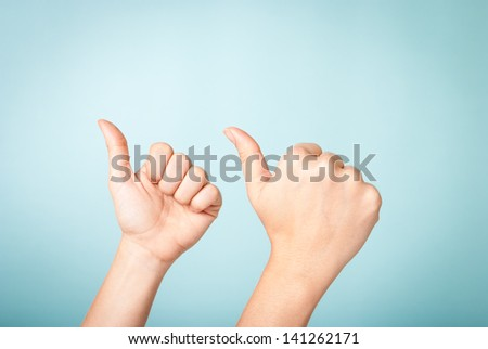 "Two hands making ""thumbs up""/like gesture over blue background, with copy space on top. Social media and business concept. - stock photo"