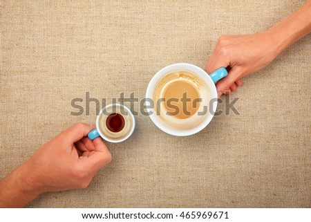 Two hands, man and woman, holding finished empty coffee cups, small espresso and big latte cappuccino, together over linen canvas background