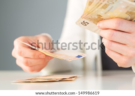 Two hands of a female counting money or paying with cash. - stock photo