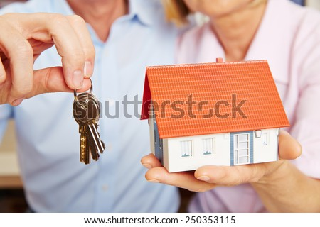 Two hands of a senior couple holding keys and a little house