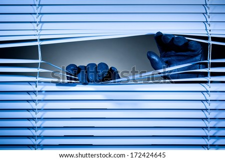 Two hands of a thief or a stalker opening closed window shutters at night. - stock photo