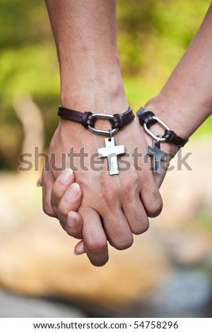 Two hands of love and Jesus's symbol. - stock photo