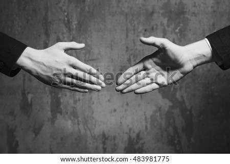 Two hands of one man stretched to each other for a handshake, a black - white picture