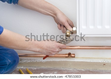 two hands of plumber with pliers and radiator - stock photo