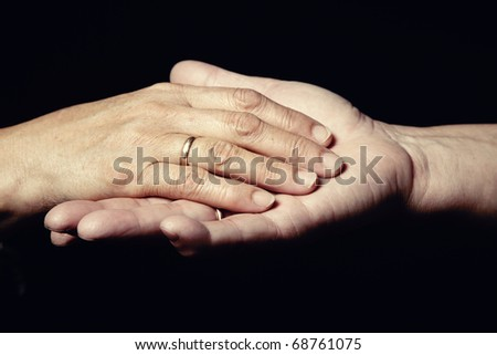 Two hands of senior people with engagement rings on a black background - stock photo
