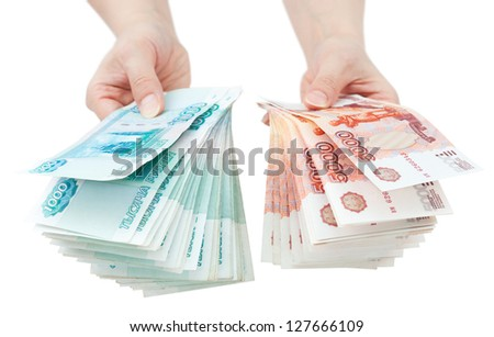 two hands offer two batches of many 1000 and 5000 rouble bills (the biggest Russian bond) - stock photo