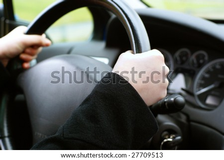 Two hands on a wheel, in the background the car interior. - stock photo