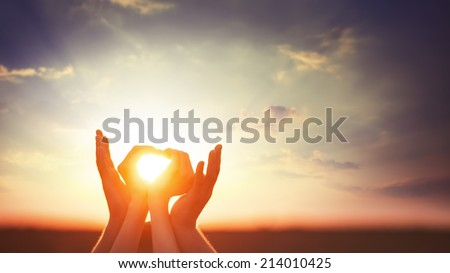 Two hands on sunset. - stock photo