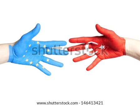 two hands, one painted with the european and one with the turkey flag on it - stock photo