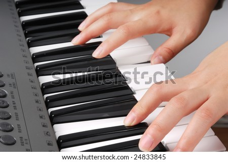 Two hands playing music on electronic organ