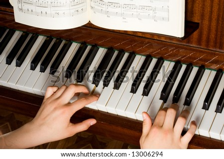 Two hands playing on the piano - stock photo