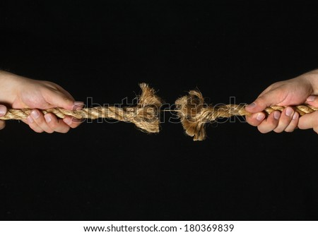 Two hands pulling frayed rope on black background - stock photo