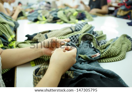 Two hands sewing an hem - stock photo