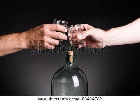 Two hands stamped glasses of vodka on the background of the bottle. - stock photo