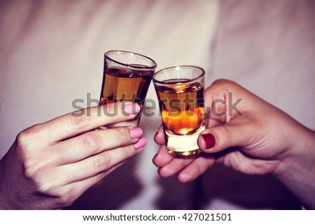 Two hands toasting whiskey on white background - stock photo