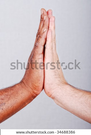 Two hands touching, black and white on background
