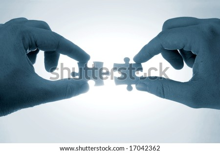 two hands trying to put together a couple of puzzle pieces in blue tone - stock photo
