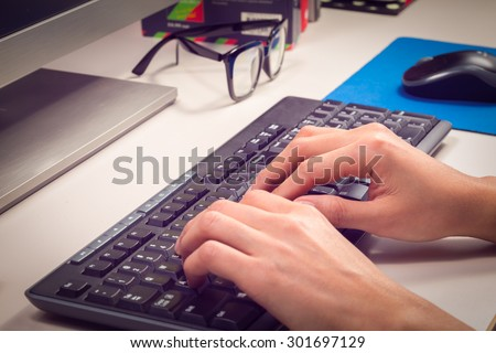 two hands typing on keyboard - stock photo