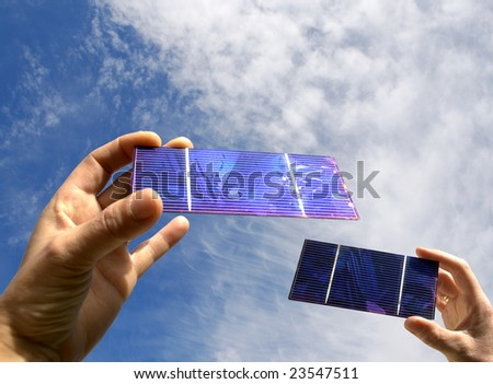two hands with solar cell against a summer sky - stock photo