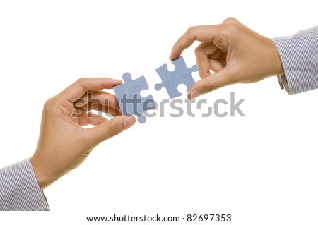 Two hands with two puzzles. Isolated over white background - stock photo