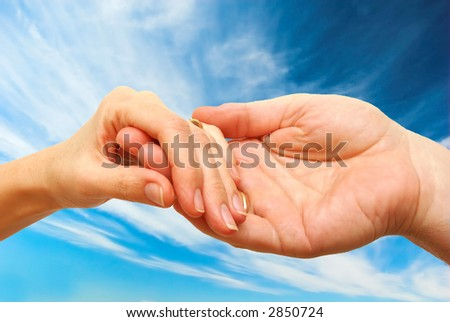 Two hands - woman and man touch each other in delicate, subtle way on sky background - stock photo