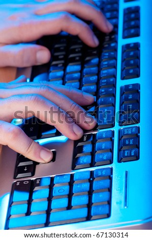 Two hands working on the silver keyboard - stock photo