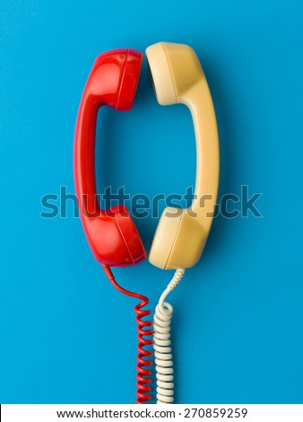 two handsets facing each other and talking on blue background - stock photo